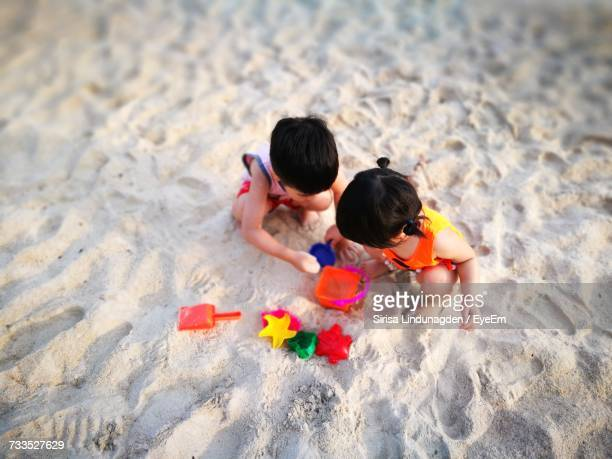 High Angle View Of Children Playing On Sand At Beach