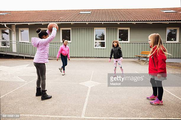 High angle view of children playing with ball in school playground
