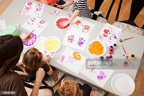 High angle view of children (2-3, 4-5) printing their hands on paper