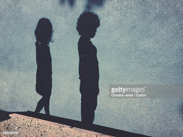 high angle view of children shadow on street - ombra in primo piano foto e immagini stock