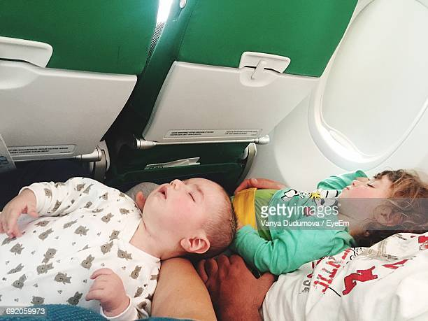 high angle view of children sleeping on laps of parents in airplane - mid section stock pictures, royalty-free photos & images