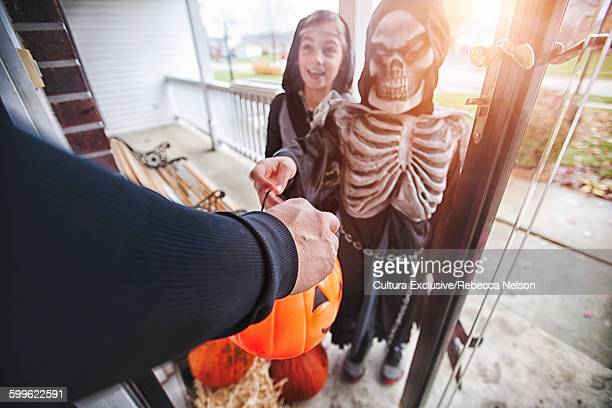 High angle view of children wearing Halloween costumes trick or treating being handed sweets