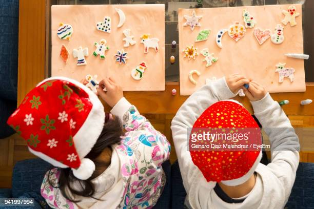 High Angle View Of Children Wearing Santa Hat Making Craft At Table
