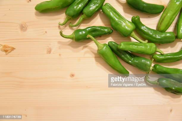 high angle view of chili pepper on table - green chili pepper stock pictures, royalty-free photos & images