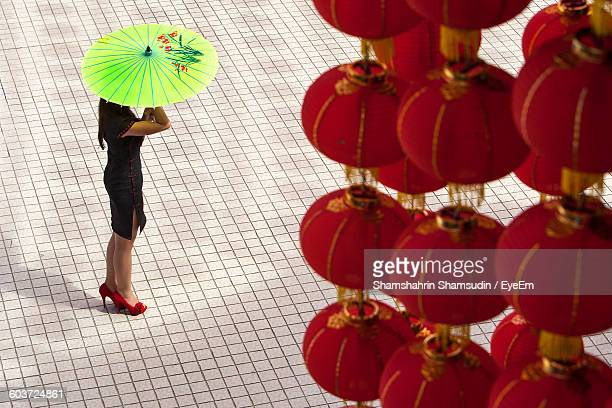 High Angle View Of Chinese Lanterns By Woman With Umbrella Standing On Footpath