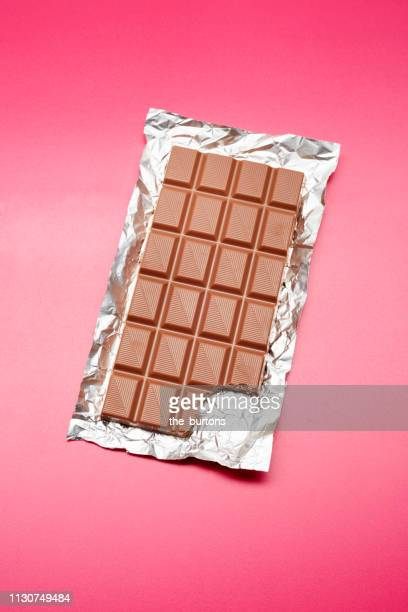 high angle view of chocolate bar on foil and pink background - chocolate bar stock pictures, royalty-free photos & images