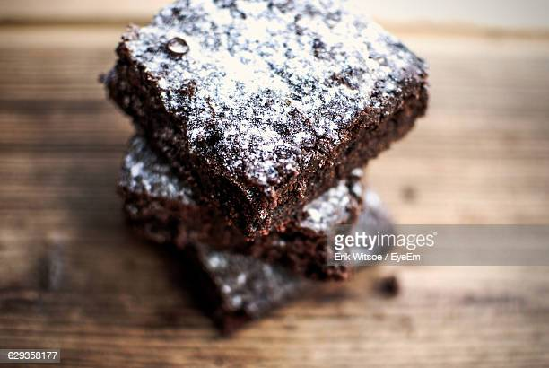 High Angle View Of Chocolate Caramel Brownie With Powdered Sugar On Table