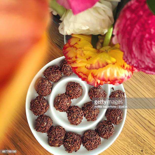 High Angle View Of Chocolate Pralines Served In Plate By Flower Vase On Table