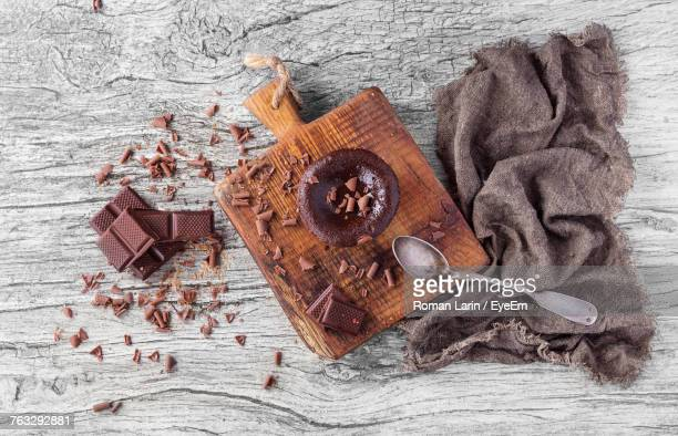 High Angle View Of Chocolates With Cutting Board And Jute On Wooden Table