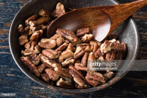 High Angle View Of Chopped Pecans In Bowl On Wooden Table