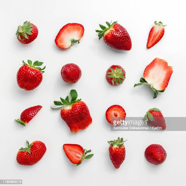 high angle view of chopped strawberries on white background - strawberry stock pictures, royalty-free photos & images