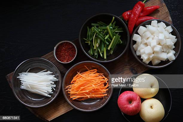 high angle view of chopped vegetables and apples on table - daikon stock photos and pictures