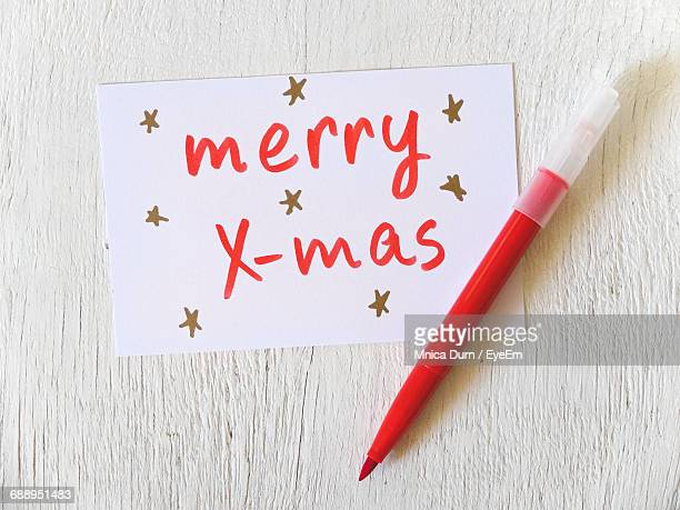 High Angle View Of Christmas Card With Red Felt Tip Pen On Table