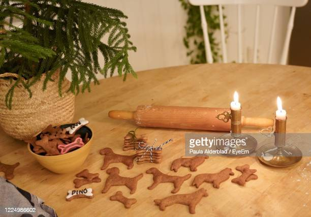 high angle view of christmas decorations on table. gingerbread cookies in the shape of dogs. - christmas decore candle stock pictures, royalty-free photos & images