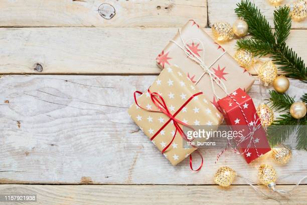 high angle view of christmas gifts and christmas decoration on wooden background - stars and strings 2019 stock photos and pictures