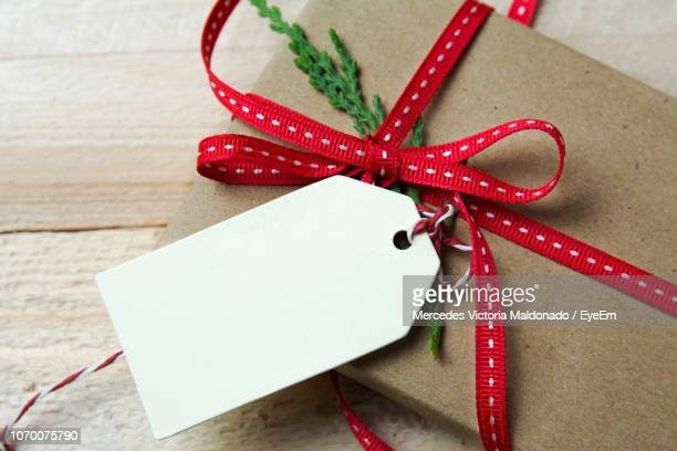 high angle view of christmas present on wooden table - christmas gifts stock photos and pictures