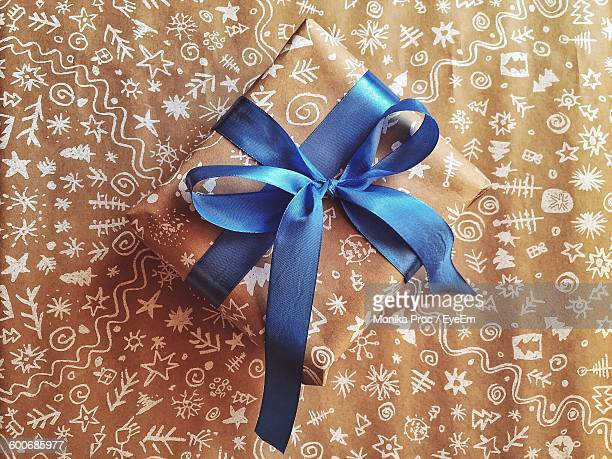 High Angle View Of Christmas Present On Wrapping Paper