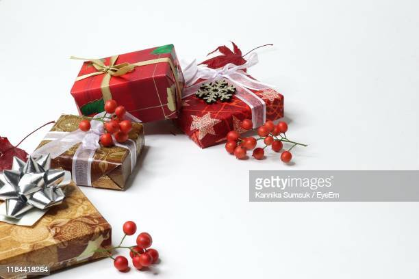 high angle view of christmas presents with cherries on white background - codogno foto e immagini stock