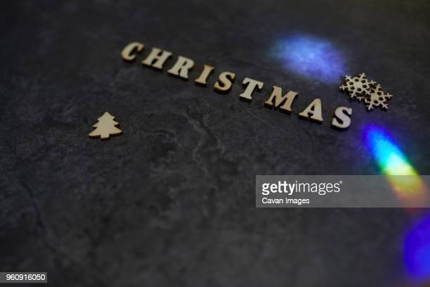 High angle view of Christmas text with decorations and light effect on table