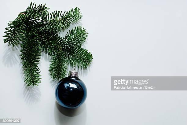 High Angle View Of Christmas Tree Leaves And Ornament On White Background