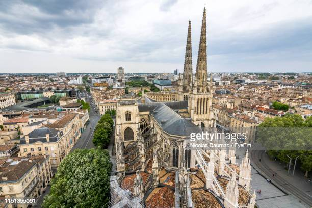high angle view of church amidst buildings against cloudy sky in city - bordeaux stockfoto's en -beelden