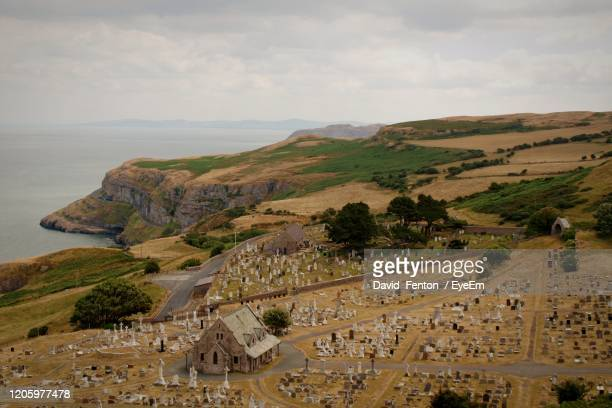 high angle view of church and cemetery against sky - llandudno wales stock pictures, royalty-free photos & images