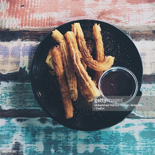 high angle view of churros and hot chocolate in plate on table - churro stock photos and pictures