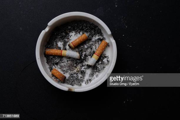 High Angle View Of Cigarettes In Ashtray On Table