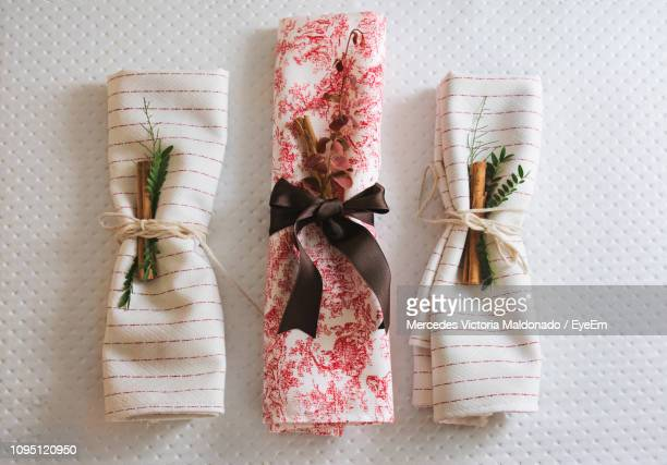 high angle view of cinnamon sticks and herbs tied with cloth on table - servet stockfoto's en -beelden