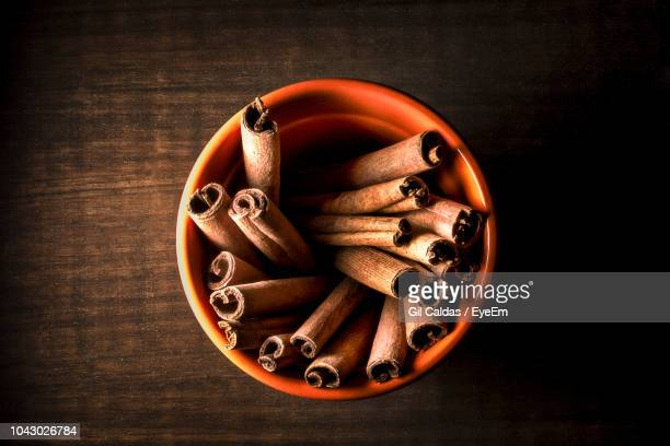 high angle view of cinnamons in bowl on wooden table - canelo fotografías e imágenes de stock