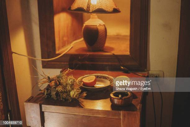 High Angle View Of Citrus Fruit On Table By Illuminated Lamp At Home
