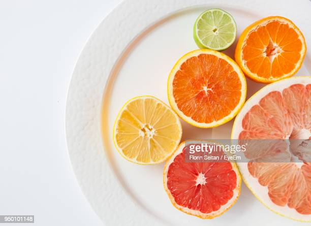 High Angle View Of Citrus Fruits In Plate Over White Background