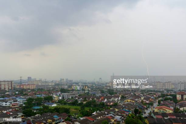 high angle view of city against cloudy sky - shaifulzamri foto e immagini stock