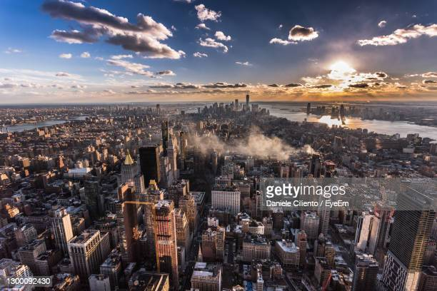high angle view of city against sky during sunset - ルポルタージュ ストックフォトと画像