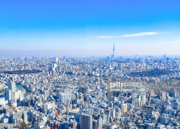 high angle view of city buildings against blue sky - town stock pictures, royalty-free photos & images