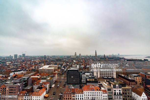 high angle view of city buildings against cloudy sky - antwerp city belgium stock pictures, royalty-free photos & images