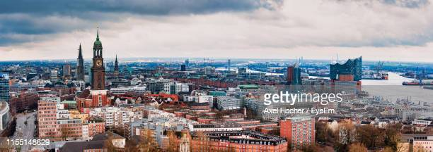 high angle view of city buildings against cloudy sky - hamburg stock-fotos und bilder