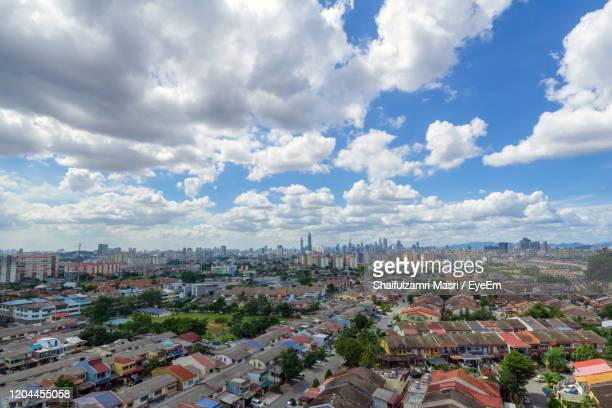 high angle view of city buildings against cloudy sky - shaifulzamri stock-fotos und bilder