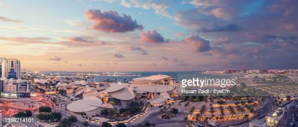 high angle view of city buildings against cloudy sky - qatar stock pictures, royalty-free photos & images