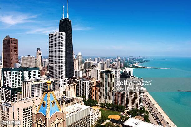 high angle view of city by sea against blue sky - willis tower stock photos and pictures