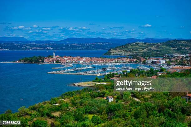 high angle view of city by sea against blue sky - koper stock photos and pictures