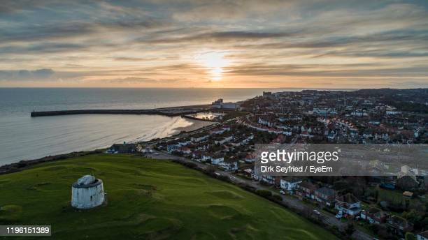high angle view of city by sea against sky during sunset - folkestone stock pictures, royalty-free photos & images