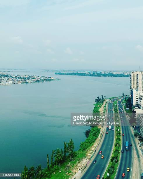 high angle view of city by sea against sky - abidjan stock pictures, royalty-free photos & images