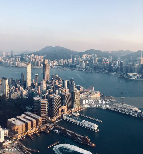 high angle view of city by sea against sky - tsim sha tsui stock pictures, royalty-free photos & images