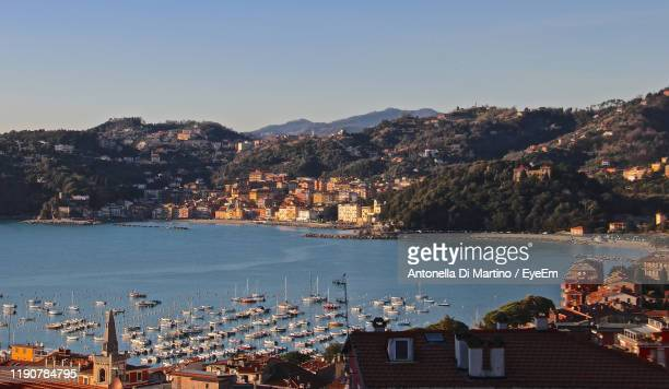 high angle view of city by sea and buildings against sky - antonella di martino foto e immagini stock