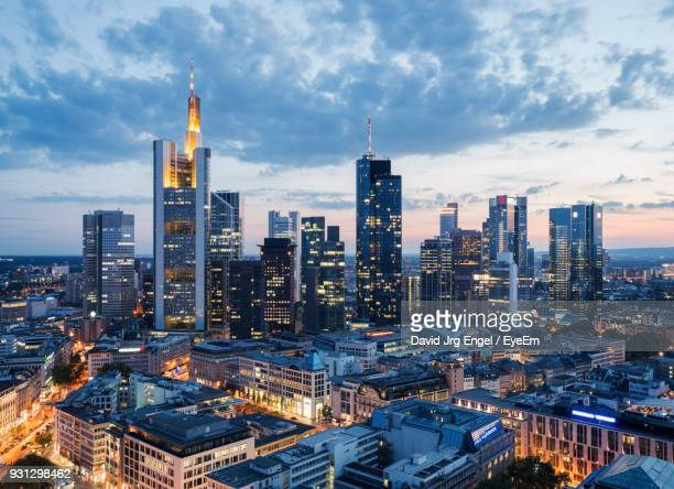 high angle view of city lit up against cloudy sky - wolkenkratzer stock-fotos und bilder