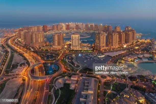 high angle view of city lit up at night - qatar stock pictures, royalty-free photos & images