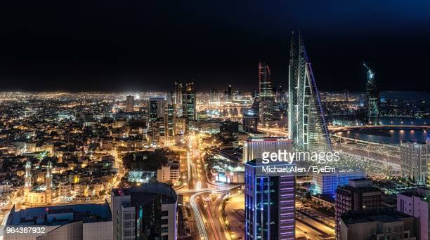 high angle view of city lit up at night - bahrain stock pictures, royalty-free photos & images
