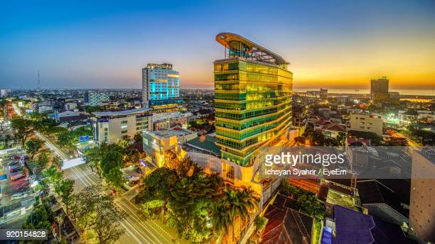 high angle view of city lit up at sunset - makassar stock pictures, royalty-free photos & images
