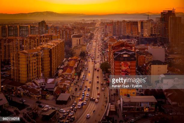 high angle view of city lit up at sunset - kosovo stock pictures, royalty-free photos & images